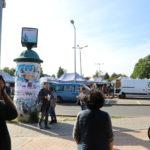 Roman Bromboszcz okleja słup ogłoszeniowy na targowisku w Mosinie