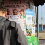 Roman Bromboszcz okleja słup ogłoszeniowy przy dworcu w Mosinie