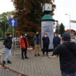 Grupa artystów bienalle przy słupie ogloszeniowym