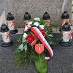 Znicze i wiązanki kwiatów przed Pomnikiem Pamięci