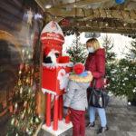 Kobieta z dzieckiem przed skrzynką na listy do Św. Mikołaja