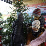 troje dzieci zawiesza ozdoby na choinkach w chatce Mikołaja