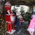 Dwoje dzieci przy skrzynce na listy do Świętego Mikołaja. Jedno dziecko wrzuca list.