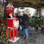 Kobieta wrzucająca list do skrzynki na listy do Św. Mikołaja