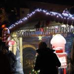 Mieszkańcy przed podświetloną chatką Mikołaja