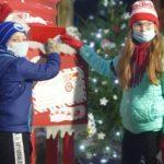 Dziewczynka z chłopcem wrzucają listy do skrzynki na listy do Świętego Mikołaja