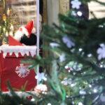 Skrzynka na listy do Świętego Mikołaja z oddali, na pierwszym planie choinka.