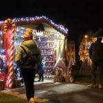 Wieczór, mieszkańcy stoją przed oświetloną chatką Mikołaja na mosińskim rynku