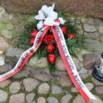 Wiązanka kwiatów przy kamieniu pamięci Piotra Mocka