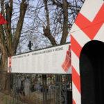 Tablica z nazwiskami mosińskich powstańców, budka strażnicza i flaga powstańcza przed cmentarzem parafialnym w Mosinie