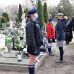 Złożenie kwiatów i zniczy przez przedstawiciela ZHP, na grobie Piotra Mocka