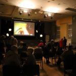 Ekran z projekcją filmu. Przed ekranem dyskusja widzów.