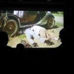 Ekran z projekcją filmu. Przed ekranem sylwetki widzów.