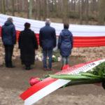 Przedstawiciele władz Gminy Mosina stojący przed obeliskiem płk. Stanisława Kasznicy. Widok z tyłu, obraz zamglony, na pierwszym planie wiązanka kwiatów.
