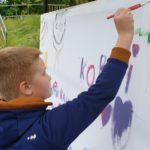 Chłopiec malujący na płótnie na blejtramie