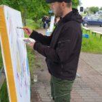 Mężczyzna malujący na płótnie na blejtramie